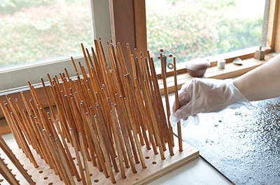 A special rack used to hold the drying chopsticks, each are worked on separately.
