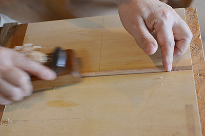 Up-close shot of Eiji planing the wooden chopstick in to shape.