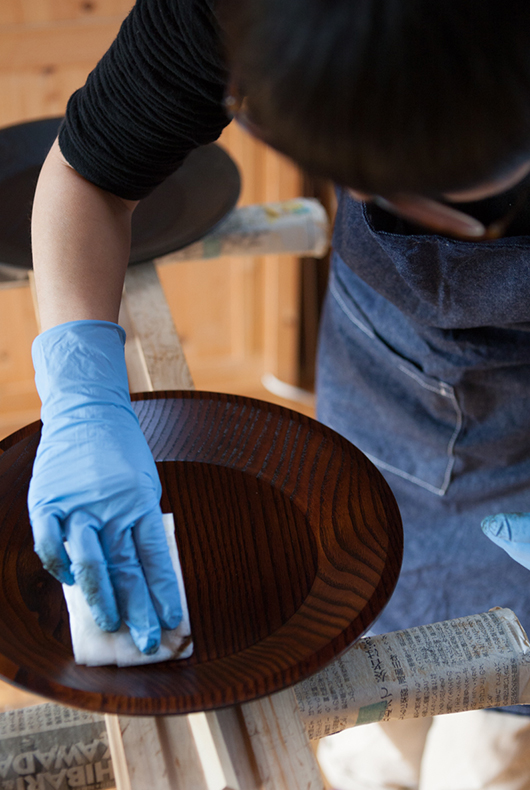 Minako touches up the surface of a lacquer dish, after leaving it to dry.