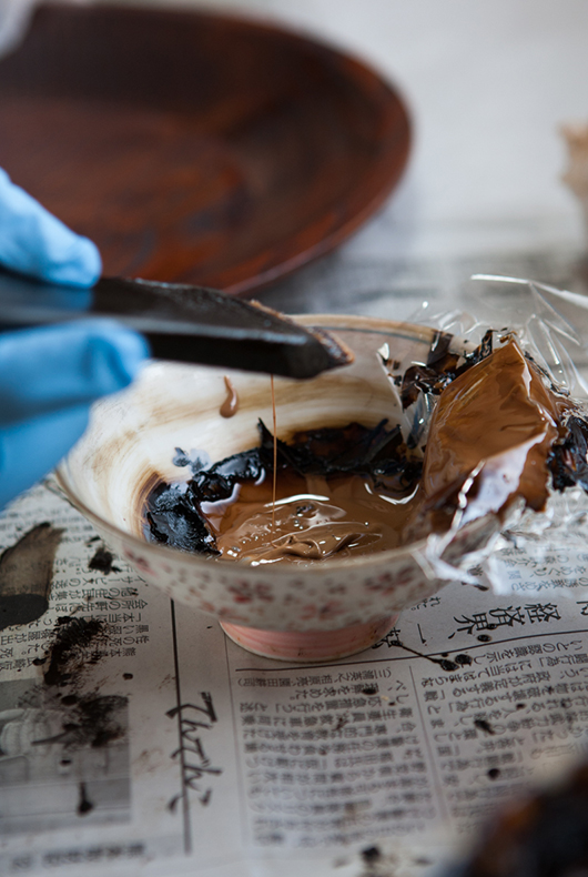 Dipping the brush in the lacquer before applying it to the dish.
