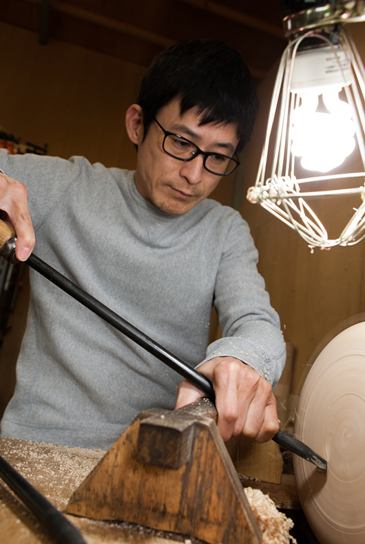 He attaches the circular plate to the lathe and starts to turn the form with precision and accuracy.