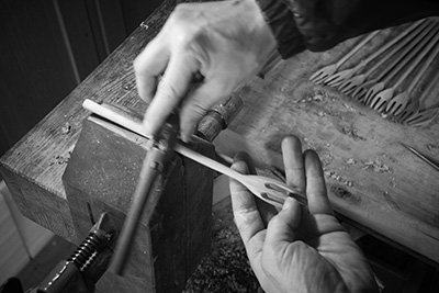He uses a sharp bladed tool to thin out the handle and create the desired shape.
