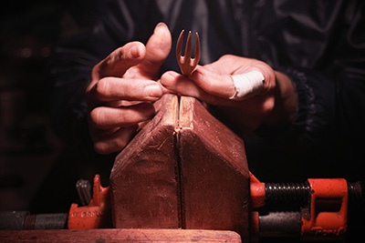 Hiroyuki puts the fork on a vice, making it easier to manipulate the wood and shave off any excess.