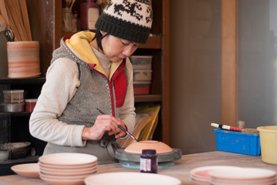 Using wax resist in her studio, this stops the foot of the bowls sticking to the kiln shelf.