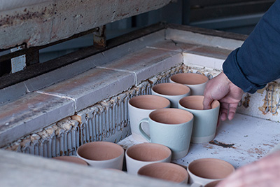 Yuichiro places some mugs in the kiln, these have been glazed and are ready to be fired.