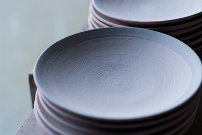 Up-close shot of the plates before they have been fired a final time in the pottery kiln.