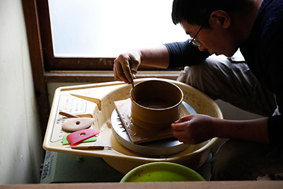 Makoto Asebi finds the right height for the plate on the pottery wheel.