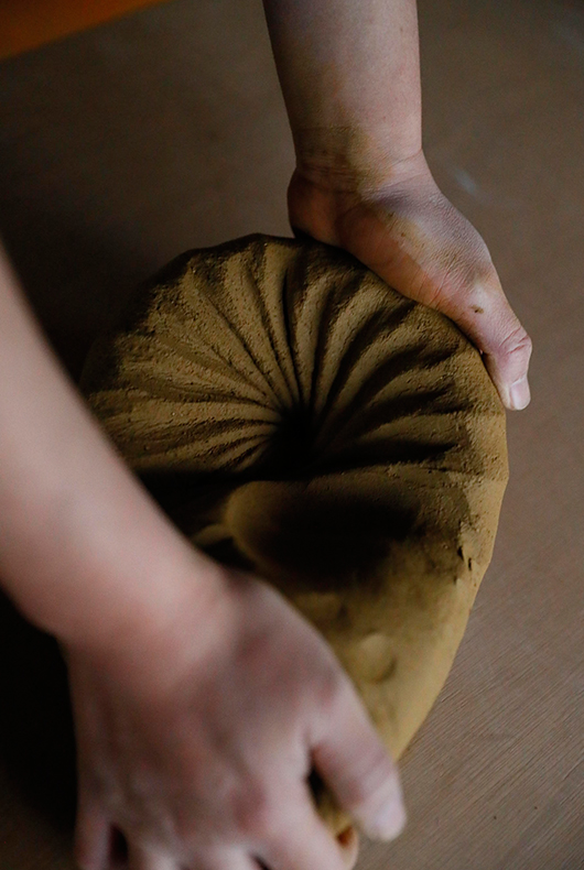 Makoto Asebi kneads the clay, making all air bubbles are removed from the clay.