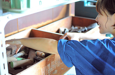 Misa reaching for tools in her workshop, she uses both hand building and wheel throwing techniques.