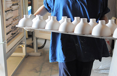 Kumabuchi carrying some of her moon bowls out of the kiln, she fires them to harden the vessels so she can apply the glaze.