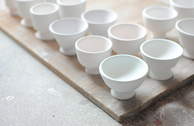 A selection of porcelain pots that have been biscuit fired in her kiln, minimal with striking poise.