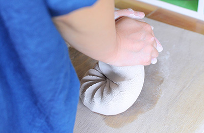 Spiral kneading porcelain clay, this releases the air bubbles and mixes the clay so it can be manipulated with ease.