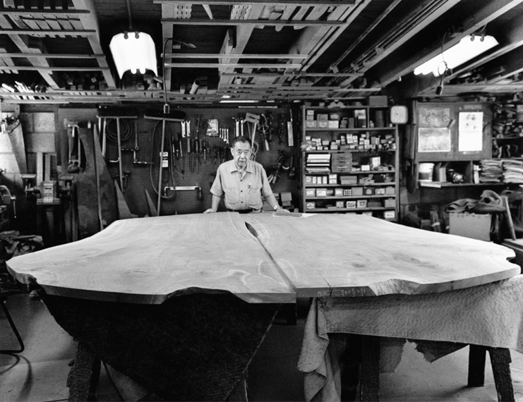 George Nakashima photographed in 1986, standing inside the workshop with one of his 'Peace Altar' tables