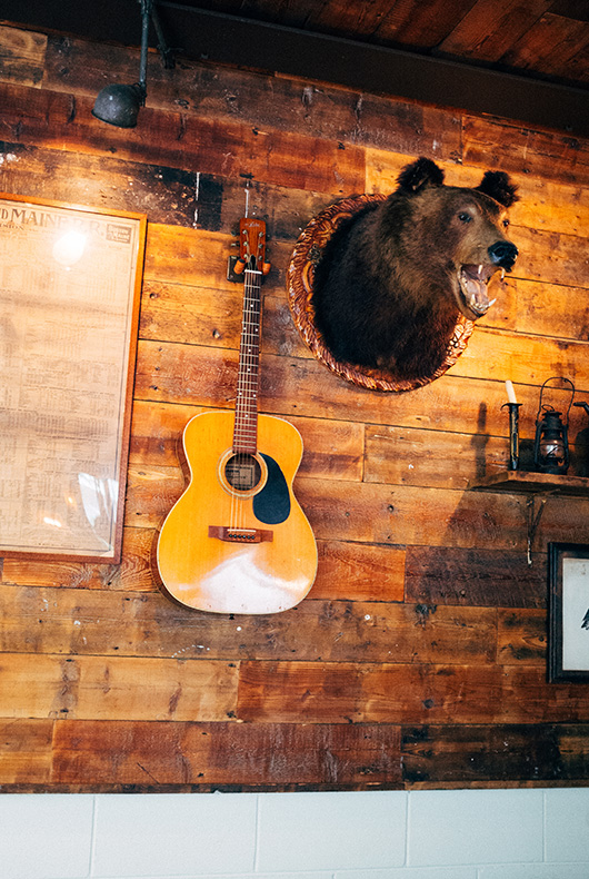 A guitar and stuffed bear head inside Bird Coffee.