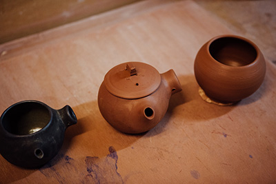 Three stages of a teapot, showing the vessel thrown from the wheel, the piece once it's been dried and all the elements attached, finally it's been glazed and finished.