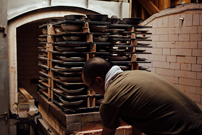 Katsufumi pulling out the pieces of pottery from the kiln.