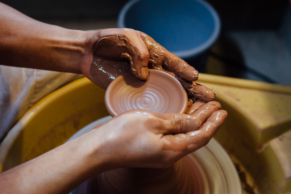 Making the lid for a teapot on the wheel by opening up the clay using his hands.