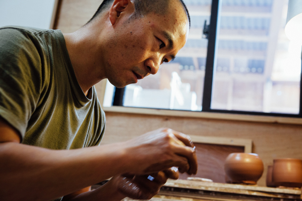 Katsufumi Baba shaping the pot on the wheel using clay.