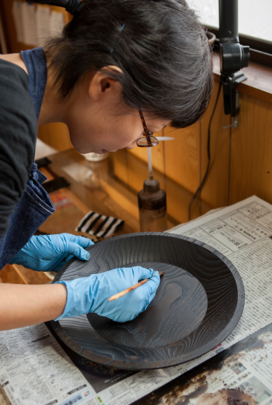 Touching up the surface of a lacquer dish in the Fujii Workshop.