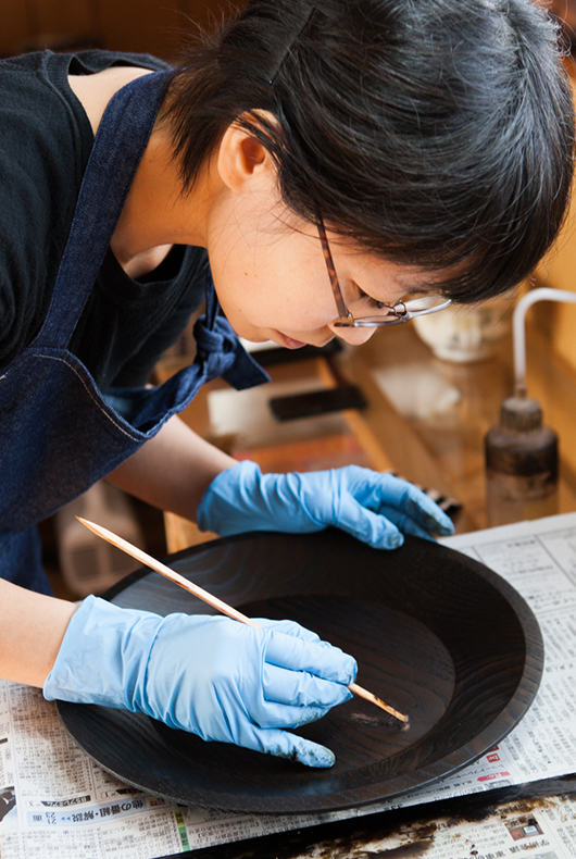 Minako touches up the surface of the large lacquer dish.