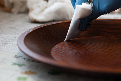 Touching up the surface of a lacquer dish with Minako Fujii of Fujii Workshop.
