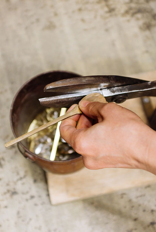 Cutting the spoon in to shape using a special set of metal cutters.
