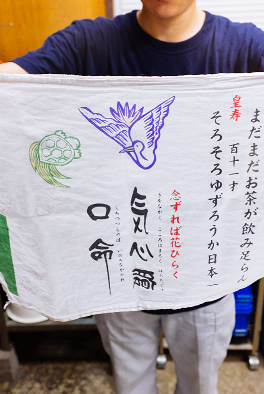 Rieko Fujimoto's holding her family scarf banner.