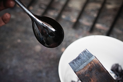 He paints the lacquer on to the spoons, slowly building up the layers and letting them dry naturally.