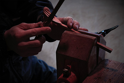 Here he starts to shape the head of a fork, using a sharp blade to perfect the form.