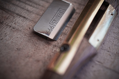 Up-close, the sharp bladed tool that he uses to shave the wood off.