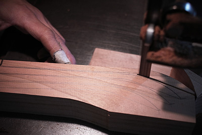 He cuts around using a badnsaw where he has drawn on the wood, making sure he is as economical as possible.