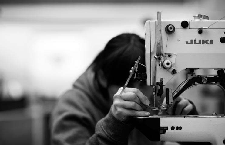 Inside the Hiut Denim factory, threading the needle. Shot by photographer Nick Hand.