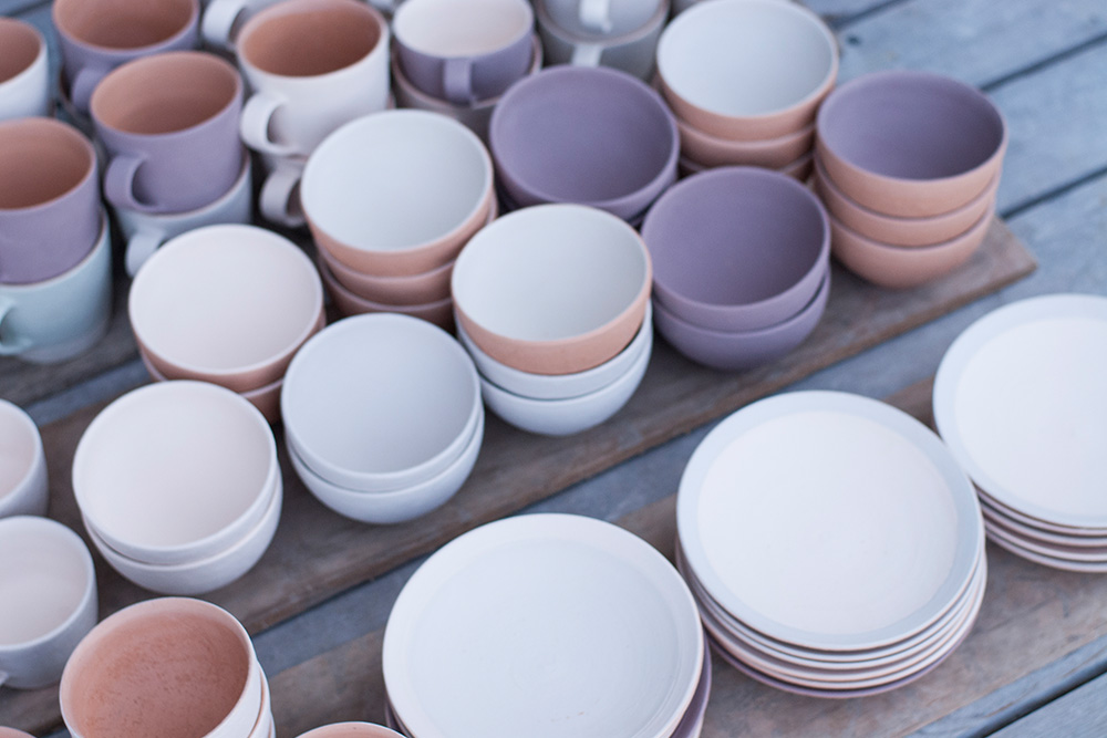 Different coloured pots that are waiting to be loaded in to the kiln.