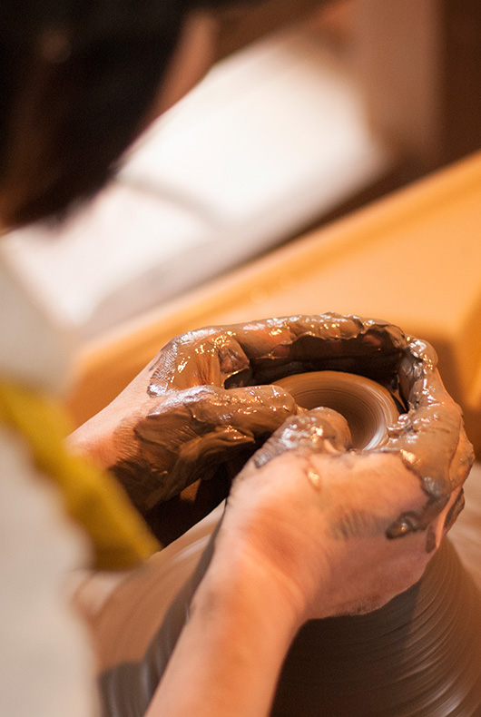 Satoko works the clay on the wheel to start opening the shape of a bowl.