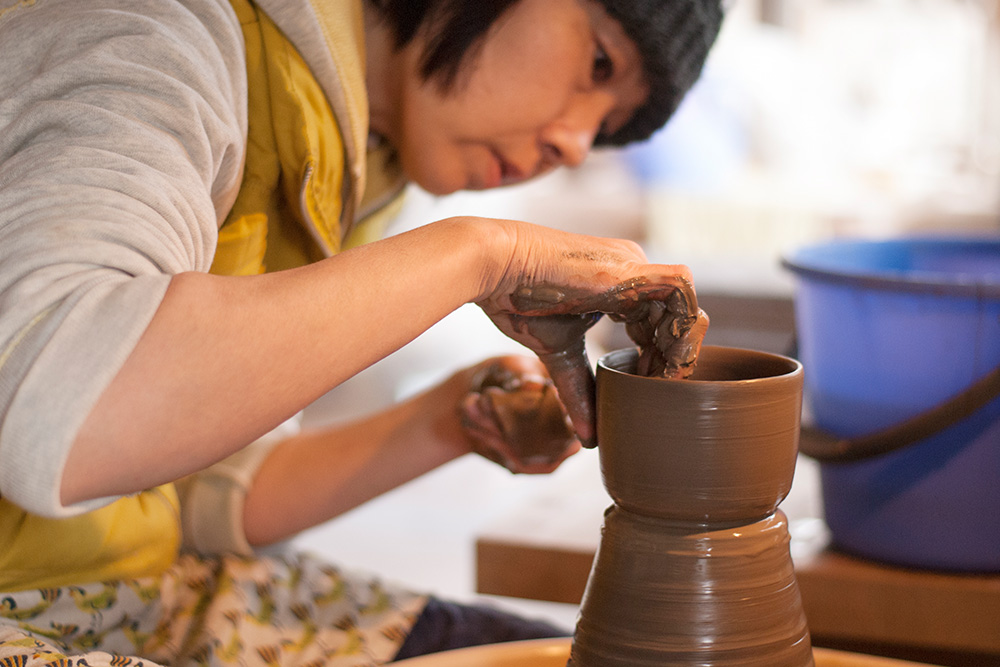 Satoko pulls up the walls of the pot, making sure they're even.