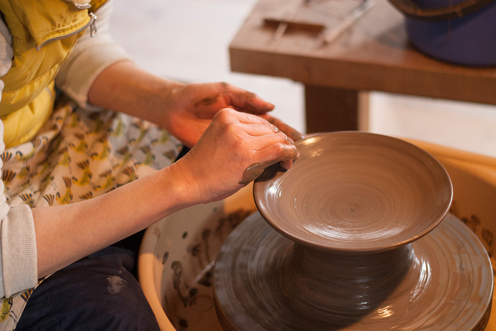 Here Satoko makes a plate, pulling the clay outwards to make a flat surface.