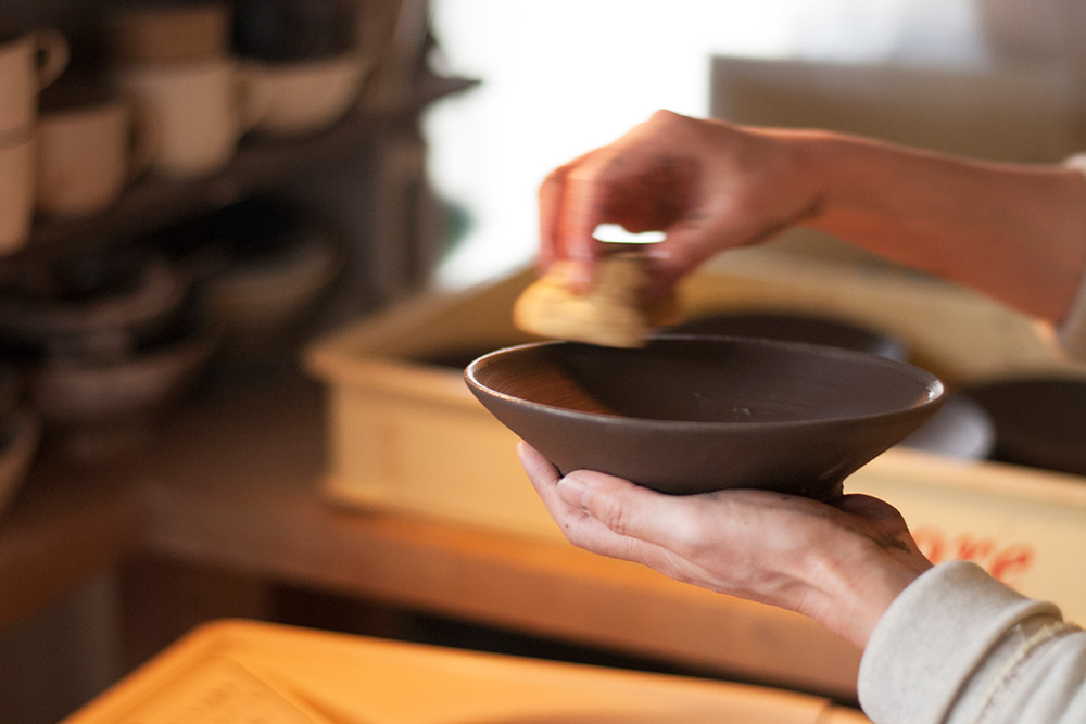 Wiping the edges of a bowl to make sure there are not sharp edges.