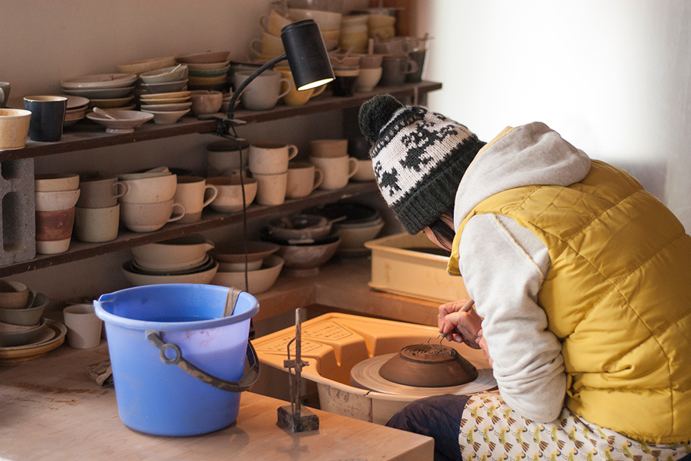 Satoko starts to trim the pottery of the bowl, getting rid of the excess clay left from the throwing process.