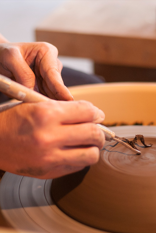 Close up photo of Satoko Suzuki trimming the base of a bowl.