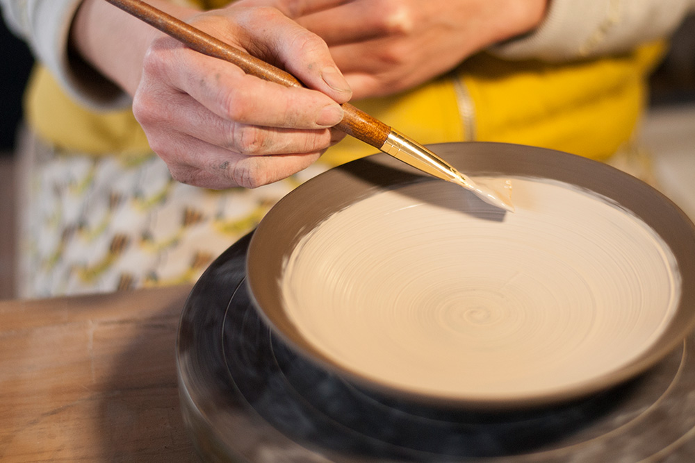 She then applies a slip to the bowl, this will coat the textured body below and add a colour base to the piece.