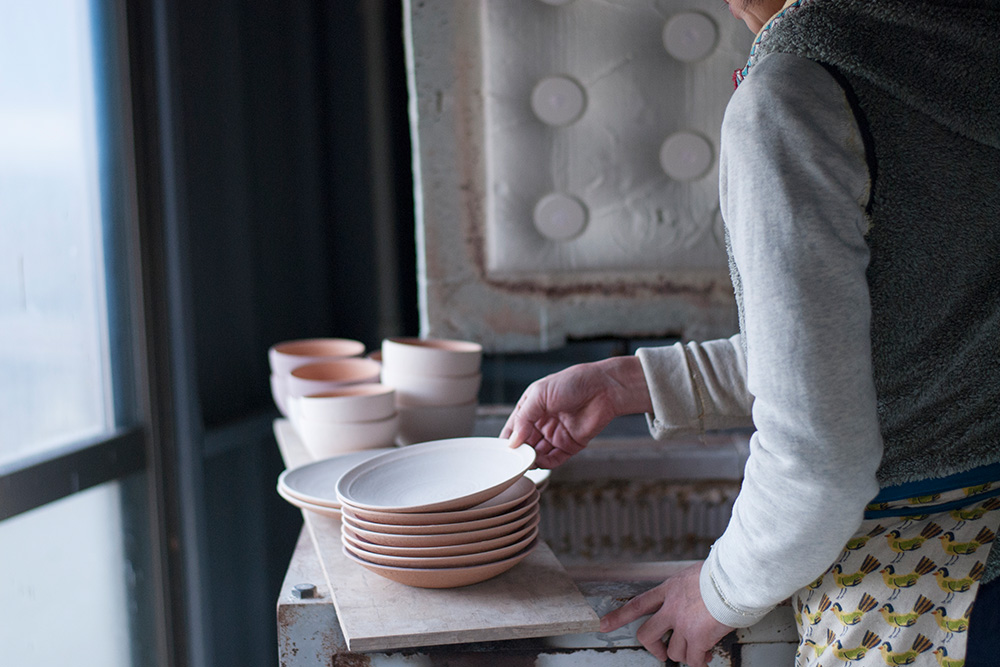 Satoko loads up the kiln with plates and bowls, these have been fired once and a glaze has been applied.