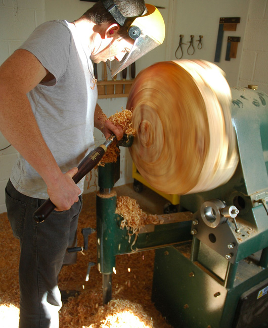 Jonathan Leech Turning a big bowl on the lathe in his workshop.