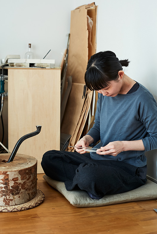 Naho Kamada examining the metal before she makes the works by hand.