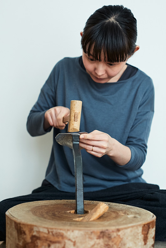 Naho Kamada begins to hammer the surface of the metal, working from the sides and turning it up to shape the form.