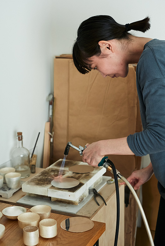 Naho Kamada uses a blow torch, making the metal malleable and easy to be shaped with a hammer.