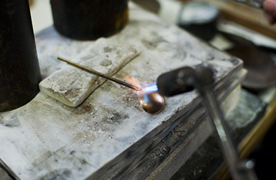 Joining the handle of the spoon to the moulded bowl with a blowtorch.