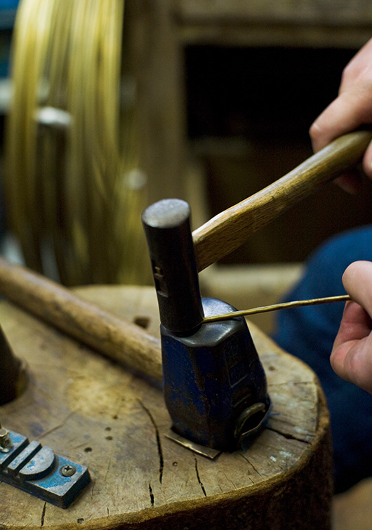 Striking the brass with a hammer to shape the handle.