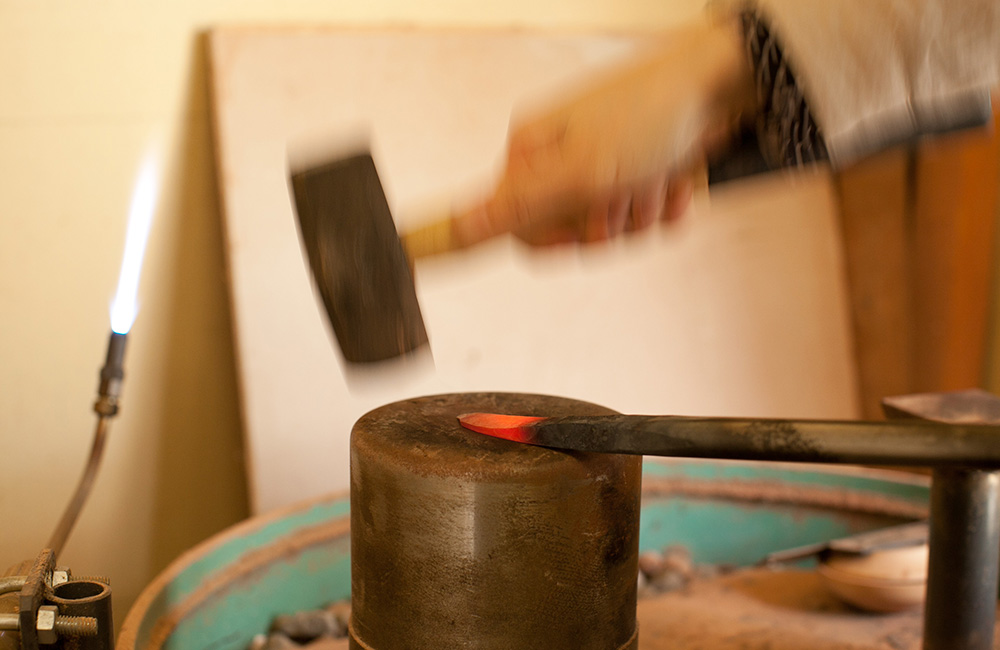 Once hot enough, Maiko can hammer the tip of the chisel to suit her needs, thus making it easier to carve her wooden objects on the lathe.