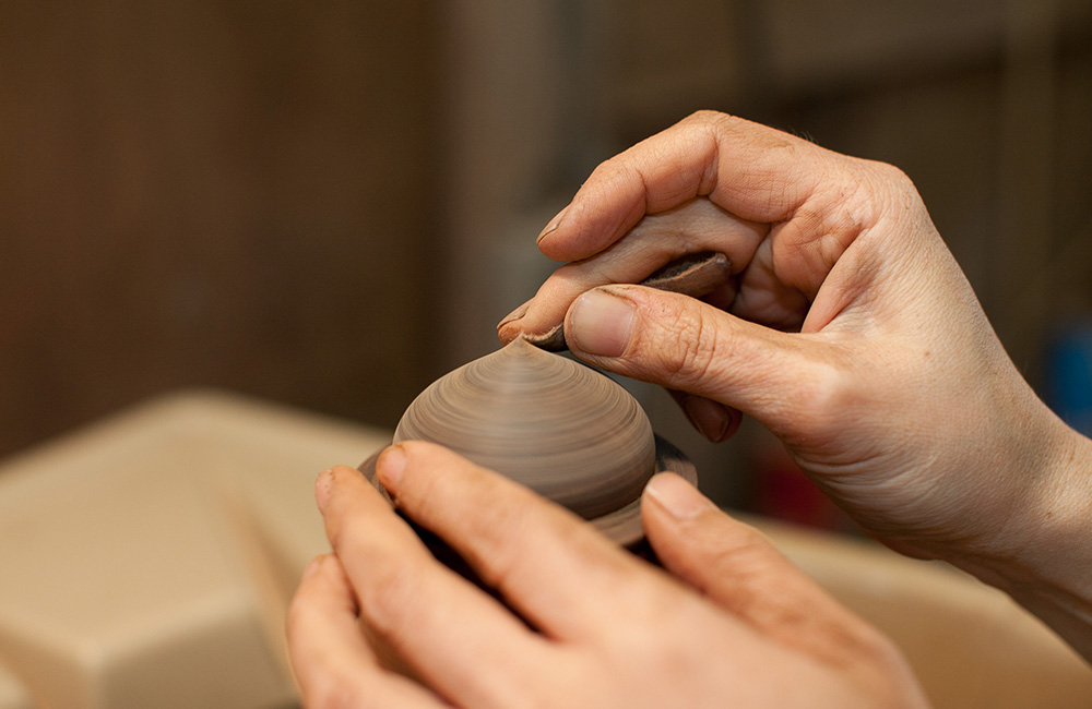 Maiko adds the first coat of lacquer to the Zelkova Dome Box, sanding the surface to get each layer evenly spread.