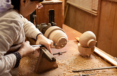 Japanese Woodturner Maiko Okuno crafting a wooden bowl on the lathe.